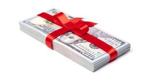 Concepto, dinero como regalo, triunfo o prima La pila de 100 billetes de dólar se ata con la cinta roja con el arco Aislado en bl Fotografía de archivo libre de regalías