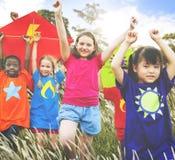 Concepto diverso de los jóvenes del campo de la cometa de los niños que juega Imagen de archivo