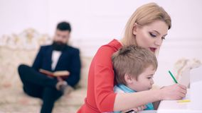 Concepto el ense?ar casero Engendre el libro de lectura, mientras que la madre ense?a al preescolar del hijo a dibujar o a escrib almacen de metraje de vídeo