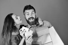 Concepto el hacer compras y del tiempo libre El individuo con la barba y la muchacha con las caras emocionadas hacen compras Foto de archivo