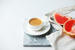 Concepto elegante del desayuno - taza de café, pomelo rojo, bolso del tejido en la placa mafble en el fondo blanco, mínimo modern imagen de archivo