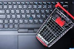 Concepto en línea de la compra y del comercio electrónico con la carretilla vacía de las compras como símbolo en el teclado del o Foto de archivo libre de regalías