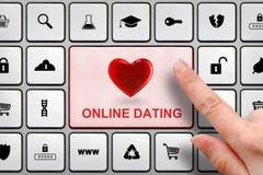 Concepto en línea de la datación, finger del ` s de la muchacha sobre el botón grande en el teclado Fotos de archivo libres de regalías