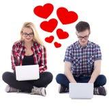 Concepto en línea de la datación - hombre joven y mujer que se sientan con los ordenadores portátiles Imagen de archivo libre de regalías