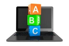 Concepto en línea de la educación. Ordenador portátil moderno con los cubos del juguete de ABC Imagen de archivo