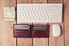 Concepto en línea de las compras con la cartera, el dinero y el teclado en fondo de madera fotos de archivo libres de regalías