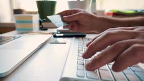 Concepto en línea de las compras El hombre incorpora la información de la tarjeta de crédito para las compras en línea metrajes