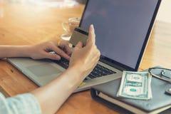 Concepto en línea de las compras, compras de la mujer usando la PC del ordenador portátil y tarjeta de crédito Fotografía de archivo
