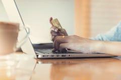 Concepto en línea de las compras, compras de la mujer usando la PC del ordenador portátil y tarjeta de crédito Fotos de archivo