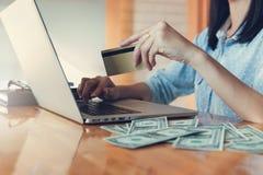 Concepto en línea de las compras, compras de la mujer usando la PC del ordenador portátil y tarjeta de crédito Foto de archivo