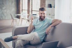 Concepto en línea de las compras Retrato de la sentada hermosa del hombre joven imagenes de archivo