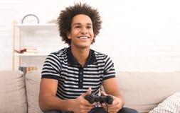 Concepto en línea del juego Individuo que juega al videojuego del fútbol con la palanca de mando fotos de archivo libres de regalías