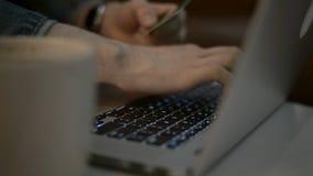 Concepto en línea que hace compras La mujer da sostener la tarjeta de crédito y usar el ordenador portátil almacen de metraje de vídeo