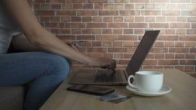 Concepto en línea que hace compras La mujer da sostener la tarjeta de crédito y usar el ordenador portátil, vídeo del hd de la cá almacen de video