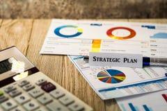 Concepto estratégico de las finanzas del negocio de la inversión del plan con las cartas y los gráficos en el tablero de madera foto de archivo