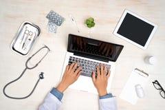 Concepto físico Doctor que trabaja con el ordenador portátil en la oficina imagen de archivo