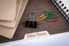 Concepto falso de la información de las noticias Registro de la carpeta en un escritorio de madera oscuro fotos de archivo libres de regalías