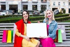 Concepto feliz de la gente - mujeres hermosas con los panieres Sostenga un letrero blanco para su texto imágenes de archivo libres de regalías
