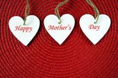 Concepto feliz del día del ` s de la madre Corazones de madera blancos decorativos en un fondo rojo de la paja Fotos de archivo