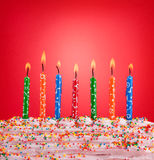 Concepto festivo Velas del feliz cumpleaños en fondo rojo Foto de archivo libre de regalías