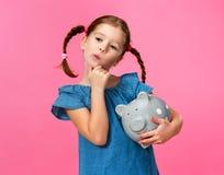 Concepto financiero del dinero suelto de los ni?os muchacha del ni?o con la hucha en un fondo rosado coloreado fotos de archivo