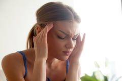 Concepto fuerte del dolor de cabeza, mujer joven que da masajes a los templos, sufferin Fotografía de archivo libre de regalías