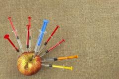 Concepto genético de la modificación Fruta y syginge Apple que recibe una inyección de alguna sustancia para la maduración rápida fotografía de archivo