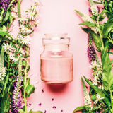 Concepto herbario natural del cosmético del cuidado de piel Tarro de cristal con las hierbas y las flores poner crema y frescas e foto de archivo