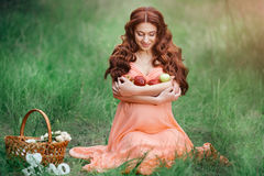 Concepto hermoso del embarazo Mujer feliz morena que se sienta en hierba con el pelo rizado en fondo de la naturaleza Imagenes de archivo