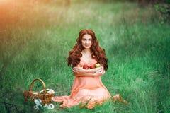 Concepto hermoso del embarazo Mujer feliz morena que se sienta en hierba con el pelo rizado en fondo de la naturaleza Fotografía de archivo