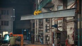Concepto industrial Planta de la construcción Una grúa que saca el haz del hierro de una estructura suspendida metrajes