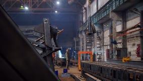 Concepto industrial Una gr?a que levanta un detalle grande Gente que trabaja en la planta almacen de metraje de vídeo