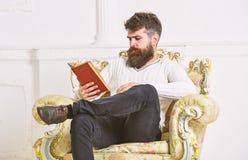 Concepto inteligente El científico, profesor en cara pensativa explora la literatura El hombre con la barba y el bigote se sienta fotos de archivo libres de regalías