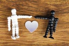 Concepto interracial del amor con las estatuillas de madera en el fondo de madera fotos de archivo libres de regalías