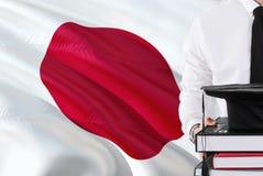 Concepto japonés acertado de la educación del estudiante Sostener los libros y el casquillo de la graduación sobre fondo de la ba fotografía de archivo libre de regalías