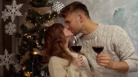 Concepto joven de la Navidad de los pares en casa junto en casa que celebra besarse de los glasss del vino almacen de video