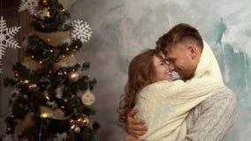 Concepto joven de la Navidad de los pares en casa junto en casa que se coloca de abrazo almacen de video