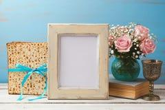 Concepto judío de Pesah de la pascua judía del día de fiesta con el marco de la foto del cartel, el matzoh y el ramo color de ros Imagen de archivo