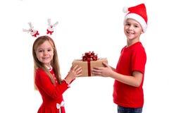 Concepto: la Navidad o día de fiesta de la Feliz Año Nuevo Muchacho feliz con el sombrero de santa en su cabeza y una muchacha co fotografía de archivo