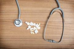 Concepto médico con las píldoras y el estetoscopio en la tabla de madera Fotos de archivo