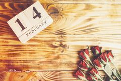 Concepto mínimo del día de tarjetas del día de San Valentín del St en fondo de madera Rosas rojas y caledar de madera con el 14 d Imágenes de archivo libres de regalías