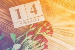 Concepto mínimo del día de tarjetas del día de San Valentín del St en fondo de madera Rosas rojas y caledar de madera con el 14 d Imagen de archivo libre de regalías
