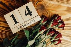 Concepto mínimo del día de tarjetas del día de San Valentín del St en fondo de madera Rosas rojas y caledar de madera con el 14 d Fotos de archivo