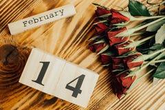 Concepto mínimo del día de tarjetas del día de San Valentín del St en fondo de madera Rosas rojas y caledar de madera con el 14 d Foto de archivo libre de regalías