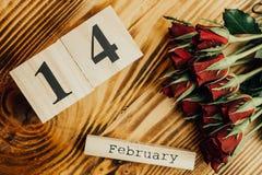 Concepto mínimo del día de tarjetas del día de San Valentín del St en fondo de madera Rosas rojas y caledar de madera con el 14 d Fotografía de archivo libre de regalías