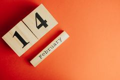 Concepto mínimo del día de tarjetas del día de San Valentín del St en fondo rojo caledar de madera con el 14 de febrero en él Imágenes de archivo libres de regalías