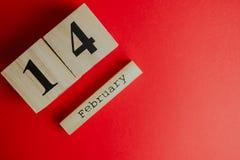 Concepto mínimo del día de tarjetas del día de San Valentín del St en fondo rojo caledar de madera con el 14 de febrero en él Fotografía de archivo