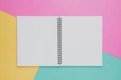 Concepto mínimo del lugar de trabajo de la oficina Cuaderno en blanco en el amarillo, rosado Imágenes de archivo libres de regalías