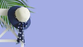 Concepto mínimo del verano de ejecución del sombrero de la mujer en la silla blanca Fotos de archivo libres de regalías