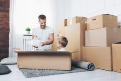 Concepto móvil, padre e hijo moviéndose a un nuevo hogar imágenes de archivo libres de regalías